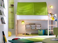 A small kids' bedroom with plenty of space for both sleep and play, with a KLURA loft bed in solid pine and a green KURA bed tent