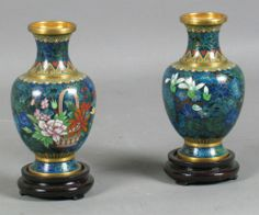 "PR CHINESE CLOISONNE VASES Pair of Chinese cloisonne vases, shaded blue and black floral ground, decorated with mirror image polychrome flower baskets, blue enamel bottom, comes with wooden base. No mark. Size: 5 1/4""H, 1 3/4""Diam. top, 3 1/4""Diam. widest part, 1 7/8""Diam. base. Condition: minor wear."