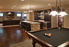 Now THIS is a GREAT BASEMENT IDEA.   You have seating, a bar, with dishwasher, and a pool table.  (Just wonder how you get that down a narrow stair way!  And you can watch the football game sitting in front of a fire, or playing pool??