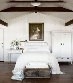 The owners of this Northern California home installed railroad trestles as beams in their bedroom. A flea-market oil portrait watches over the antique iron bed, covered with Pottery Barn's fisherman-knit blanket. The walls and ceiliing are painted Kelly-Moore's White.