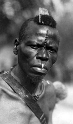 Africa | A man with a comb in his hair, facial scarification and a lip ring. Congo. || Scanned vintage postcard; photographer C Zagourski.