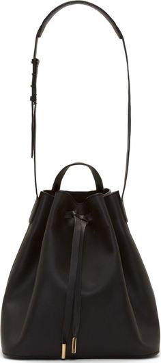 "Structured buffed leather bucket bag in black. Matte effect throughout. Gold-tone hardware. Adjustable shoulder strap. Grab handle at opening. Drawstring closure at main compartment. Zippered pocket at interior. Fully lined. Tonal stitching. Approx. 10"" length, 11"" height, 7"" width."
