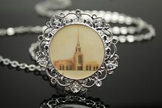 This Gila Valley Temple necklace was created from the original art of LDS artist Clayton K Vance. Clayton found a passion for hand drawing architectural elevations while attending the University of Notre Dame, where he received his Masters Degree in Classical Architecture. Clayton has used his artistic skills and architectural knowledge to create a whole new perspective on LDS Temple art. This classical technique is the same that would have been used in the original elevation drawings for…