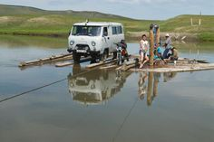 Picture of an archaeology expedition pulling a wooden ferry across a river