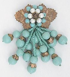 Miriam Haskell dress clip is a pair of Russian gold plated leaves with a ring of aqua glass beads around a ring of faux pearls around a gold tone center set with an unusual filigree bead. Varying lengths of aqua glass bead dangles hang from the bottom of the centerpiece, each with a pair of larger aqua beads at the end of a strand of small aqua beads.