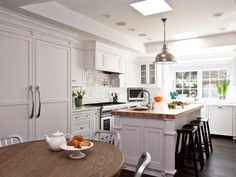 HGTV presents a white transitional kitchen with a stainless steel pendant light hanging over an eat-in kitchen island with butcher block countertop.