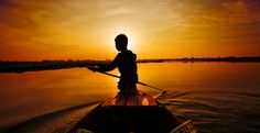 Panorama of child rowing boat into the setting sun in Phnom Penh, Cambodia    by Ben Heys