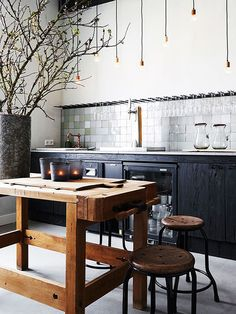 black lower cabs (no uppers), wooden island & stools, high ceiling