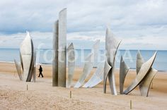 Lone man walks on beach in Normandy, France through the blades of a large metal sculpture placed on the sands of Omaha Beach.