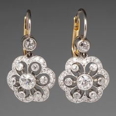 A stunning pair of circa dangle style pierced earrings featuring a platinum setting centered with one bezel set diamond surrounded by six bezel set diamonds and 30 bead set diamonds, all old European cuts. Ear Jewelry, Jewelery, Jewelry Accessories, Fine Jewelry, Jewelry Making, Antique Jewelry, Vintage Jewelry, Bijoux Art Nouveau, Custom Jewelry Design