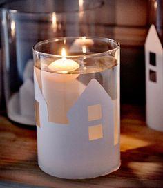 Un vaso IKEA CYLINDER decorato con la silhouette di un paesaggio in carta e riempito con acqua e una candelina galleggiante