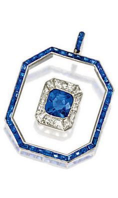 *SAPPHIRE, ROCK CRYSTAL AND DIAMOND PENDANT, CIRCA 1925 Centring on a cushion-shaped sapphire weighing 2.76 carats, framed by calibré-cut diamonds, within octagonal-shaped rock crystal edged with calibré-cut sapphires extending to the chain loop, mounted in platinum, accompanied by a white gold chain,
