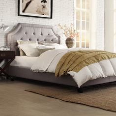 The arched bridge top curves of this elegant bed frame are defined by button tufted nickel nailhead trimming. The frame is highlighted by grey linen upholstery and poplar wood accents finished in espresso.