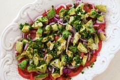 Fresh tomato, red onion, and avocado salad, seasoned Italian style with oregano, fresh parsley, garlic, olive oil, wine vinegar, salt and pepper.