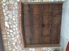 Metal garage doors painted to look like wood with fluer De Lis hardware