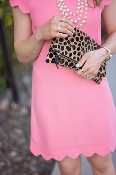Coral scalloped dress paired with pearls and a leopard clutch.