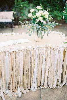 Brides.com: . Dress up your guestbook station with strips of linen to create a fanciful fringe table skirt. It's a pretty first sight for guests entering the ceremony space.