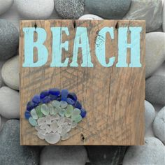 This cute sign features a sea shell design made out of beach glass (sea glass) that was found by me on the beaches of the north shore of Lake Ontario, near to Toronto. The beach glass is a mixture of white/clear, greens and blues, arranged in an ombre formation. It also features hand painted lettering BEACH in a pale blue colour. The sign is constructed on a piece of reclaimed barn board from Ontario.  This piece would make a stunning decorative piece in any home or holiday cottage.  Bea...