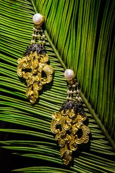 A pair of elegant feminine gold repousse carved coconut shell earrings is combining with white pearls, rose-cut black & white diamonds mounted in 9K gold and black rhodium sterling silver.  Dimension: 4.5x10x0.8 cms.    Repoussé is a metalworking technique in which a malleable metal is ornamented or shaped by hammering from the reverse side to create a design in low relief. There are few techniques that offer such diversity of expression while still being relatively economical.
