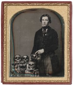A man pointing at a human skull next to a table of human skulls, c. 1850 - Imgur