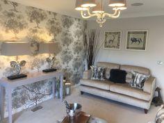 Safari theme livingroom soft pastel console table lamps feature wallpaper trees
