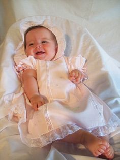 This adorable designer collection features a soft rosy pink 100% cotton batiste dress, slip and bonnet. The dress is embelished with embroidered tiny rosebuds down front and bottom and an embroidered