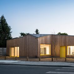 Timber slats cover the angular facades and continue across the roof of this community centre for the Bordeaux suburb of Pessac by Gayet-Roger Architects.