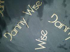 """Danny Wise Logo Toutes les garnitures de créations DANNY WISE Haute Couture sont de véritables œuvres d'art, pièces uniques, toujours en harmonie ou le contraste avec la couleur du tissu externe doublures aussi personnalisé appelé """"parlé"""" en or MK 3."""
