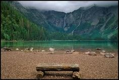 A rough hewn wood bench made of logs is sitting on the rocky shore of Avalanche Lake in the mountains of Glacier National Park, Montana. Beautiful Places, Beautiful Pictures, American National Parks, Rocky Shore, Nature View, Adobe Photoshop Lightroom, Pictures To Paint, Wonders Of The World, State Parks