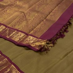"""The """"#Olive #Green"""" #handwoven #Kanjivaram #Silk #Sari from Kanakavalli is set off by a maroon with gold zari floral design border on either side. An attractive horses, elephants and floral motifs adorn the maroon pallu. The border is repeated on the maroon blouse that completes the sari."""