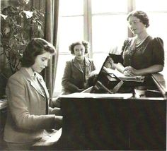 Princess Elizabeth playing piano, while her sister, Princess Margaret and Queen Elizabeth (The Queen Mother) look on.