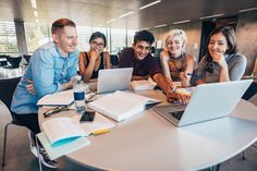 University students in cooperation with their assignment by jacoblund. Multiethnic group of young people studying together at a table looking at laptop. Young students in cooperation with ...