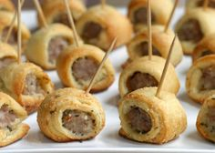 Link sausage wrapped in croissants brushed with melted butter and filled with Parmesan cheese and oregano, then cut into mini bite-size appetizers.