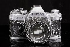 New Camera, by David Meanix (a real Canon camera covered with pieces torn from photographs of itself)