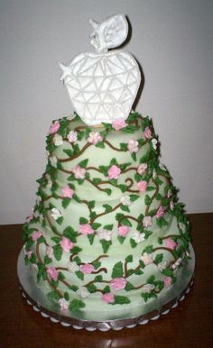 """This creation by Sweet Pea Cake Co in Colorado Springs was for a recipient of the prestigious Crystal Apple Award.  The """"Crystal Apple"""" on top is made out of royal icing and placed atop a three tier cake designed to look similar to an apple tree. The edible apple blossoms are hand piped and painted out of royal icing to cover the entire cake. (hashtags: #apple #cake)"""