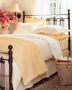 Using a light buttery yellow with white linens & a black iron bed.