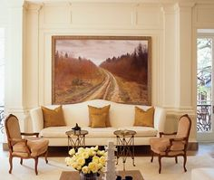 This breathtaking salon exudes luxurious style.      A large work by Russian painter Oleg Vassiliev dominates this living room. It's paired with an oversized cotton-upholstered sofa flanked by 19th-century suede-covered French chairs.