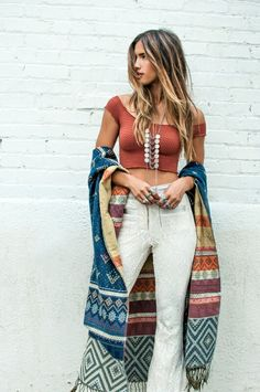 Chic over-the-shoulder crop top and white pants. Colourful, long scarf with tribal prints.