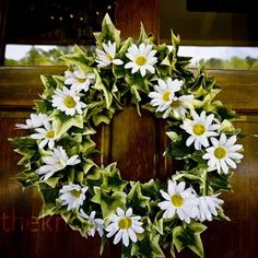 Maybe replace the daisies with lilies on a wreath of green ivy (heart shape?) to bring the color scheme together for the perfect door décor.