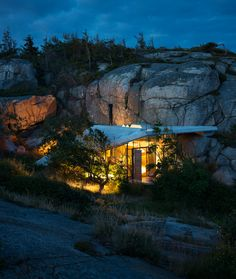 Cabin Knapphullet by Lund Hagem.  This small seaside holiday home by Norwegian studio Lund Hagem nestles against a cliff, and features a stepped concrete roof that doubles as a viewing platform.  Wedged between weather-beaten boulders double its height, Cabin Knapphullet is protected from extreme weather conditions. Its wall are glazed, but it is sheltered beneath a chunky concrete roof.