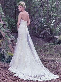 This fit and flare wedding dress features hand placed shimmering embroidered lace appliqués on tulle and a sweetheart neckline. Complete with covered buttons over zipper and inner corset closure. Lace and tulle detachable train sold separately.