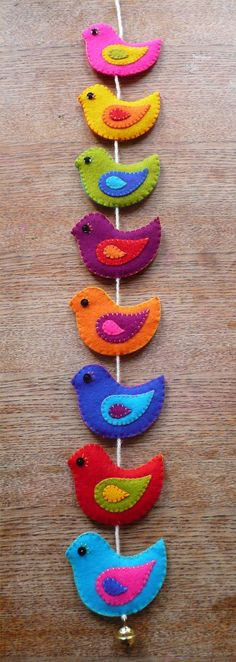 A wall hanging full of sweet colorful birds. Lovely to hang from a ceiling hook or to decorate a door, a wall or (the side of) a cupboard with. The birds are hand cut from beautifully colored wool felt and delicately embroidered on both sides. Each one of the 8 birds consists of 6 layers of wool felt. The two sides of the birds are stitched together with contrasting colors of embroidery thread. The wall hanging is finished of with a silver colored metal bell. The string measures appr…