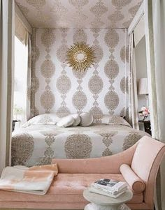 This stunning canopy bed with whites and golds was designed by Windsor Smith. I love how the pattern they used for the duvet, transcends up the wall and above onto the ceiling piece as well. I find it very bold that they used a gold metallic mirror on the metallic gold pattern, but the area needed something otherwise it would have been dead space. The salmon chaise in front of the bed really grounds all the shimmer with a subdued solid color. Beautiful job!