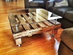 DIY pallet coffee table I made using oversized bolts and a custom sheet of glass on caster wheels