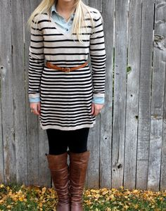 jean shirt under a stripped sweater dress matched with brown boots and a brown belt with black leggings