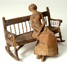 """Southern Folk Art Mud Lady.  This wonderful doll and elaborate rocking bench are made from cardboard and hardened mud. Such elegance conveyed with such a humble medium. She sits demurely wearing her fashionable dress and holding a fan, with legs crossed. The rocking bench has decorative spindles and crest rail.  Approximately 10"""" long. American, probably Southern, circa 1880."""