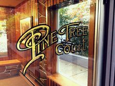 Pine Tree Court: Gold leaf lettering on glass. Original sign artist, unknown. Convex effect is a technique using oil size and water size to adhere gold to the glass. Photo by Riley Cran