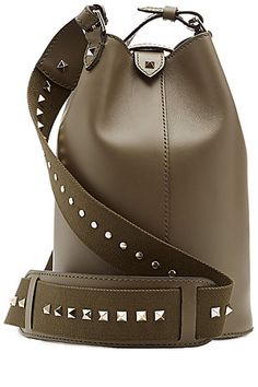Designed with a modern bucket silhouette, this Valentino shoulder bag is dotted with the brand's signature studs for a glossy contrast to the rich khaki leather #Stylebop