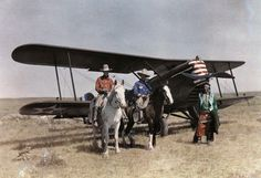. Three men stand in front of a plane on the Crow Reservation Edwiin L. Wisherd.  Autochrome