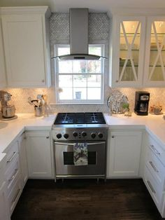 professional kitchenaid gas cooktop with convection oven. oven in front of window. stainless vent in front of window. LED vent hood with arabescato herringbone pattern backspash. white shaker cabinets. white thick slab quartz countertops. LG brand. Empire collection hardware.